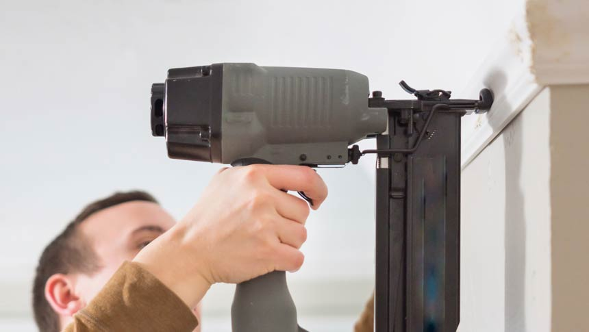 Carpenter works with cordless finish nailer